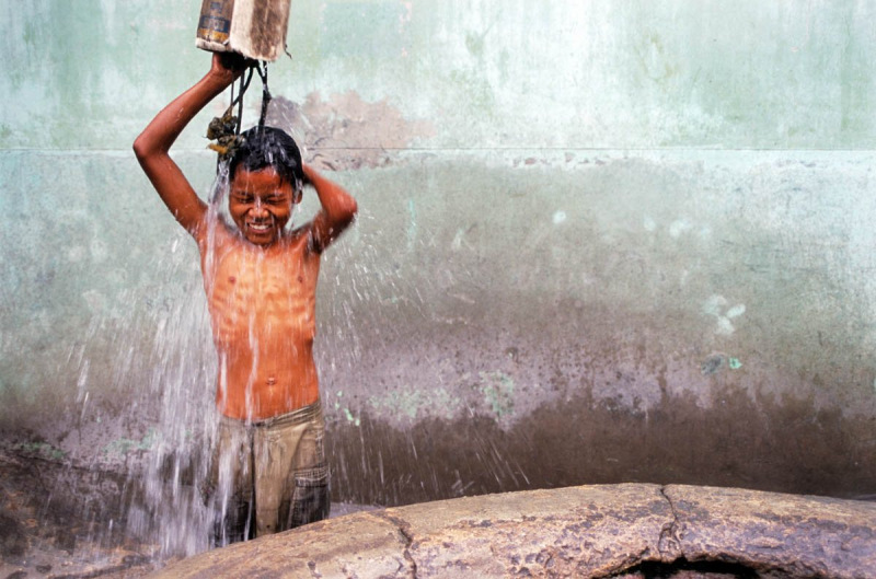 boy washing at a well in Myanmar